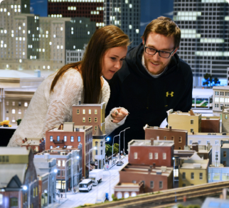A man and woman are observing the miniature houses of Little Canada. The woman is pointing at a house.
