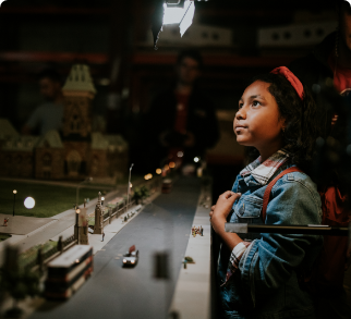 A little girl is observing the details of Little Canada while a miniature car drives by.